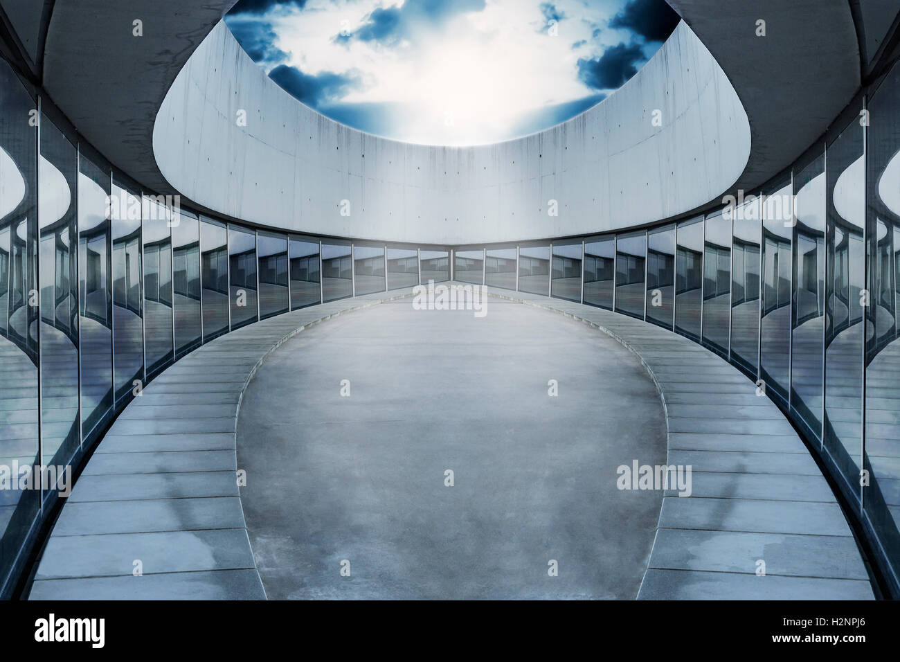 Empty oval arena with surrounding glass panels. The ceiling is open and lets the sun break through the dramatic - Stock Image