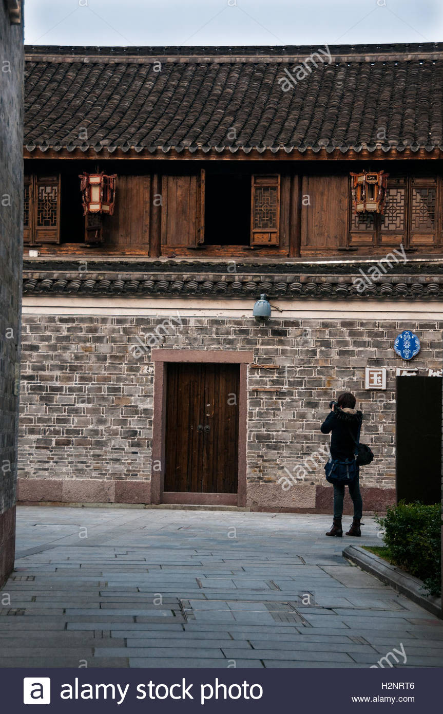 A young man take a photograph of an old building in Ningbo's Moon Lake Flourishing Garden. - Stock Image