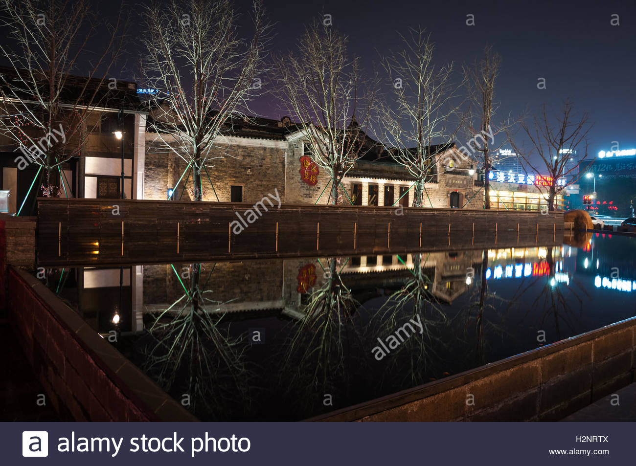 Old buildings at the Moon Lake Flourishing Garden complex reflected in water at night in Ningbo, Zhejiang Province, - Stock Image