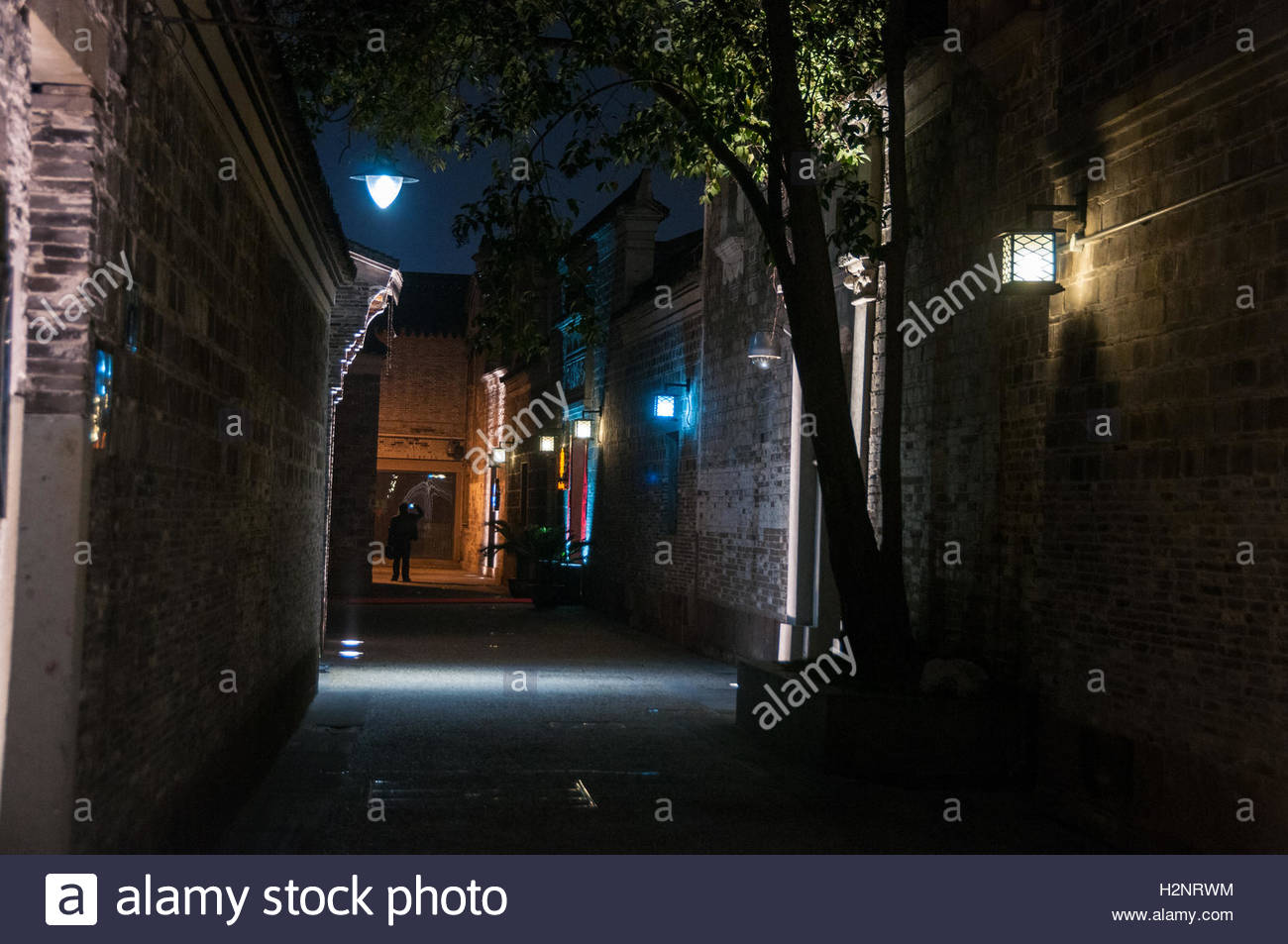 A lone man takes a picture with a mobile phone at night in a back alley of the Moon Lake Flourishing Garden, Ningbo - Stock Image