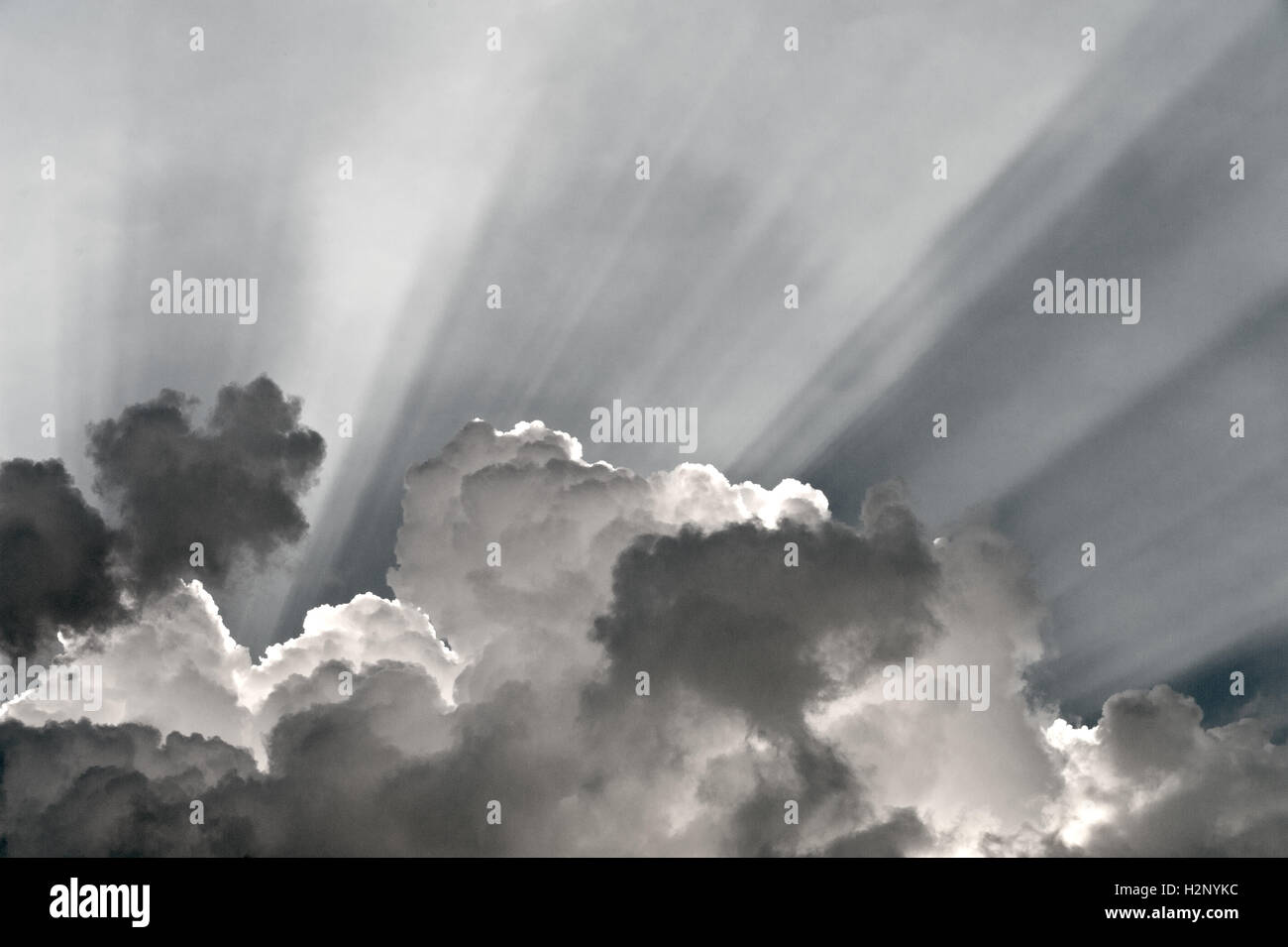 Rays of light behind dark clouds. - Stock Image