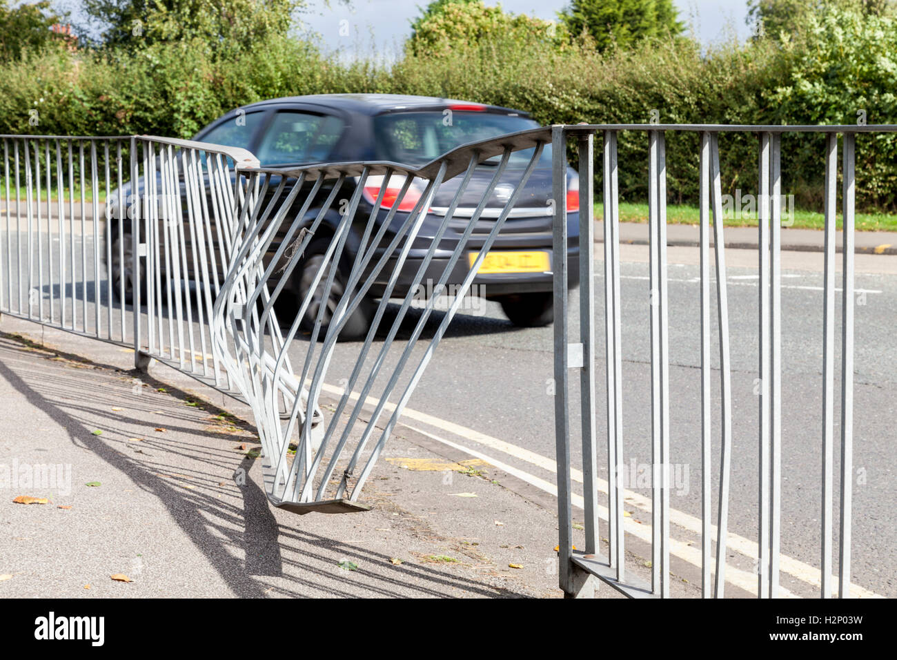 Damaged traffic barriers between the pavement and road with a car