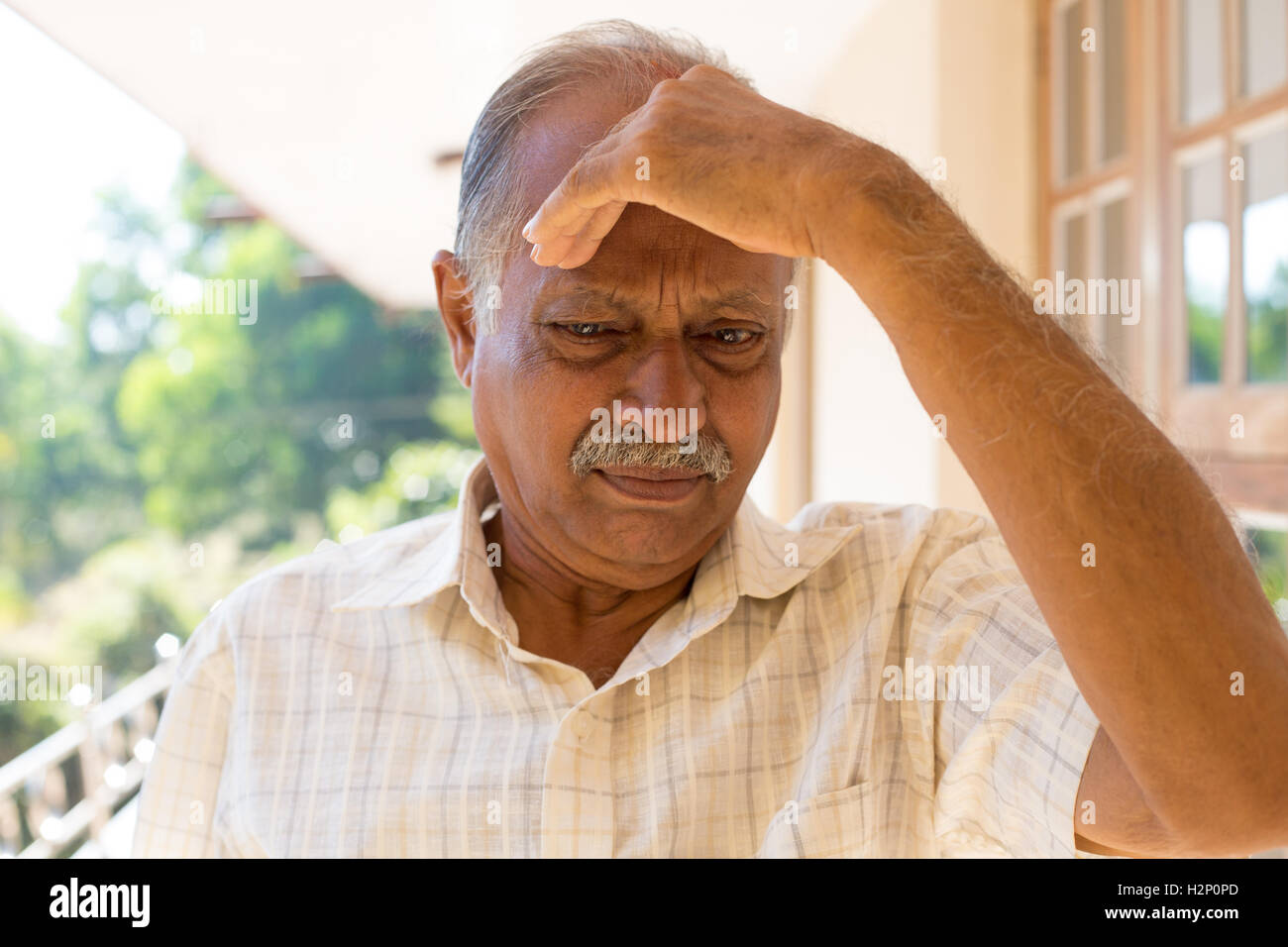 Closeup portrait, morose elderly pensioner, downcast gloomy, resting hand on head, isolated outside outdoors home - Stock Image