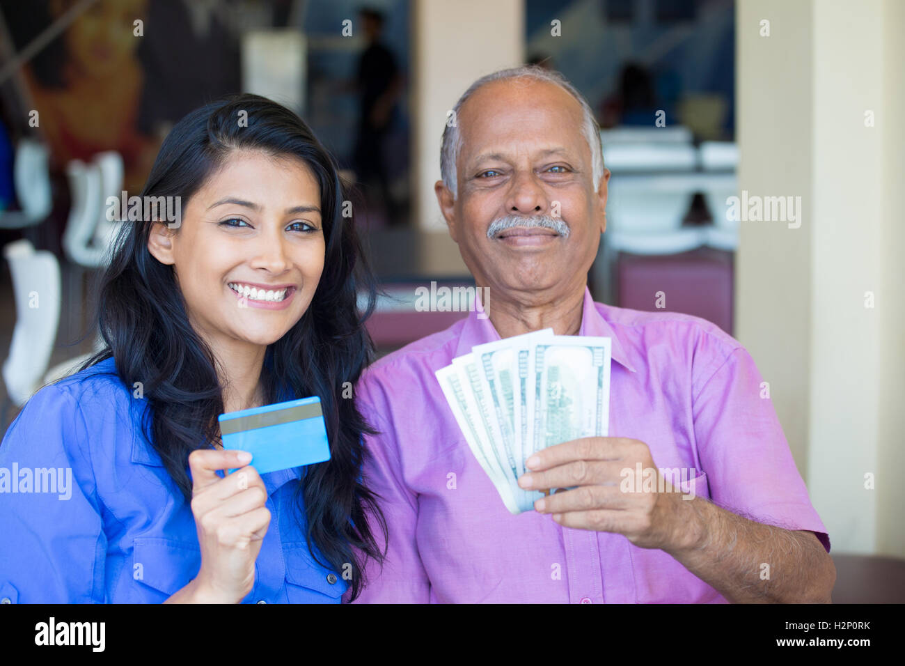 Closeup portrait rich elderly gentleman in pink shirt and lady in blue top holding greenbacks and credit card. Booming - Stock Image