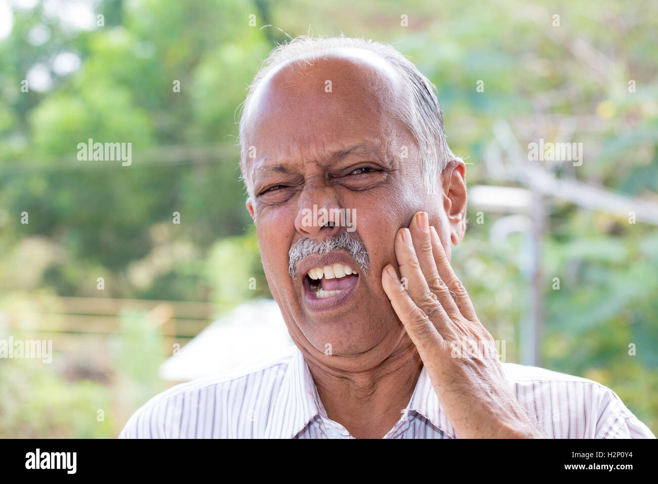Closeup portrait elderly business man with tooth ache crown problem cavity grimacing from pain touching outside - Stock Image