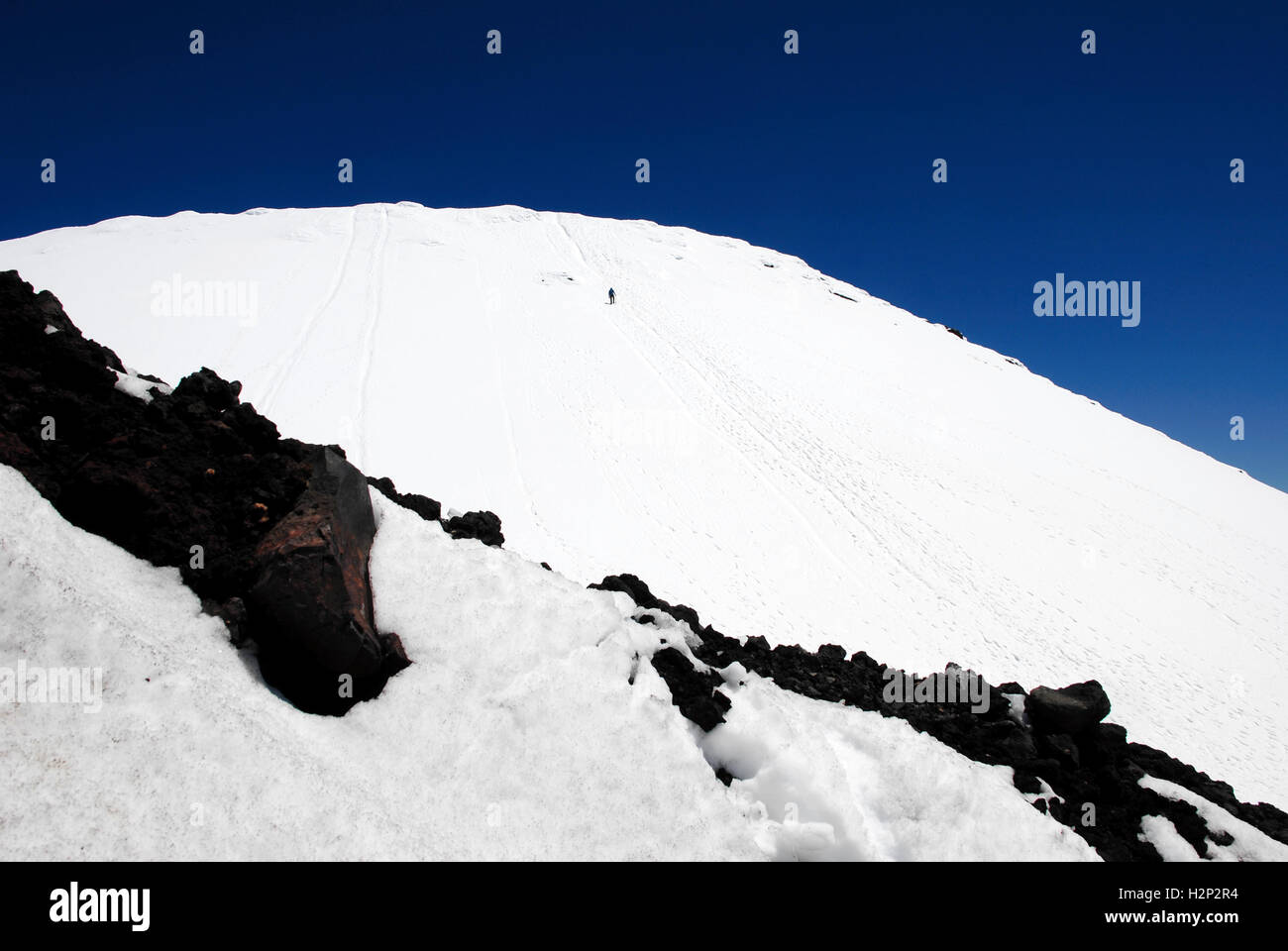 A lone hiker ascends the snow covered summit of Mount Ngauruhoe in Tongariro National Park, New Zealand. Stock Photo