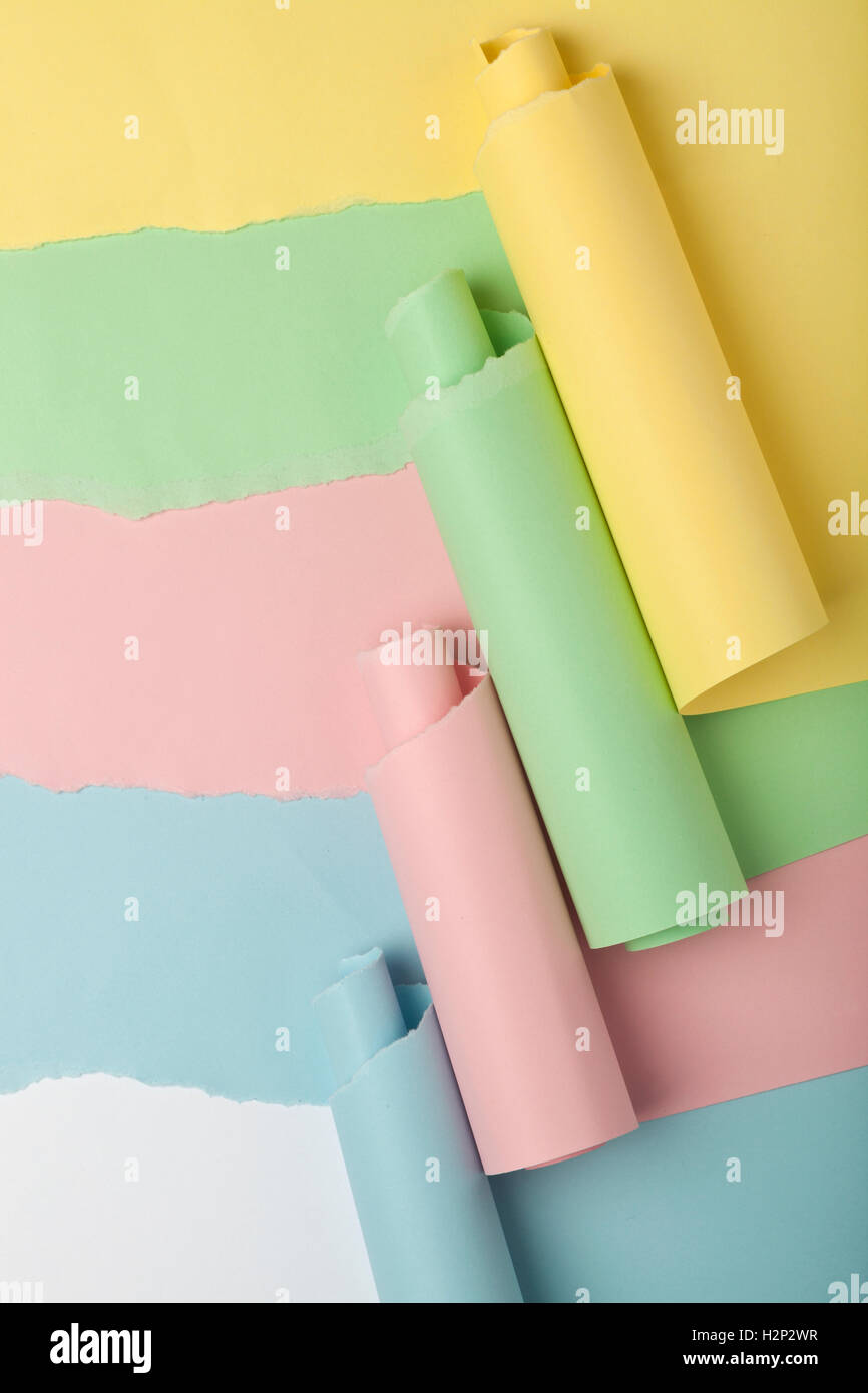 Tear in colored papers revealing white background underneath - Stock Image