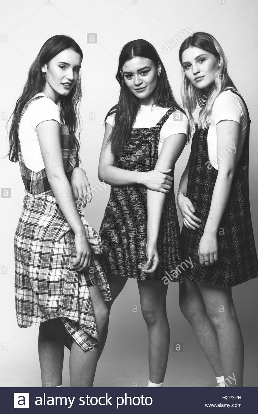 Three models wearing checked pinafore dresses in a studio location shot in black and white for a fashion lookbook - Stock Image