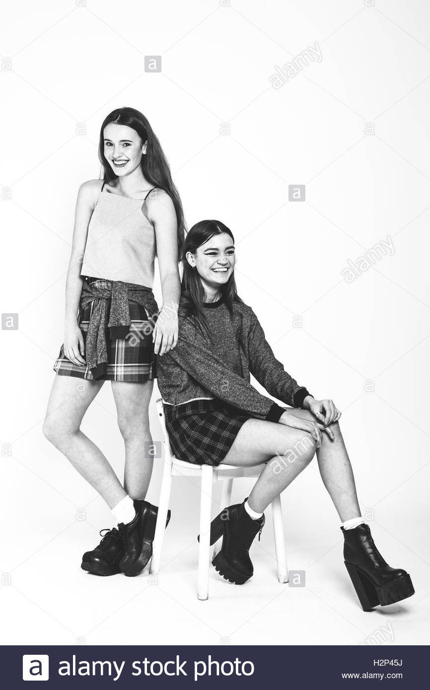 Two brunette models wearing cropped tops and tartan skirts shot in a studio in black and white. - Stock Image