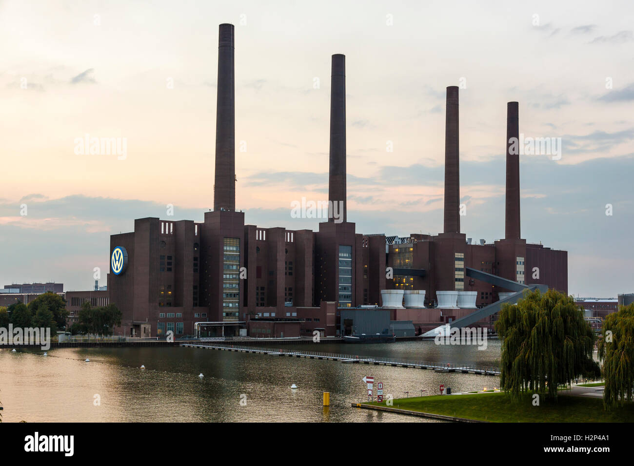 View of the old Volkswagen factory building with the illuminated VW logo Stock Photo