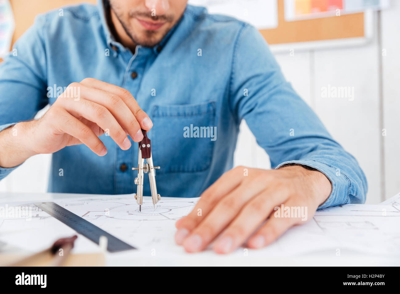 Cropped image of a architect working on construction blueprint in office with divider at office - Stock Image