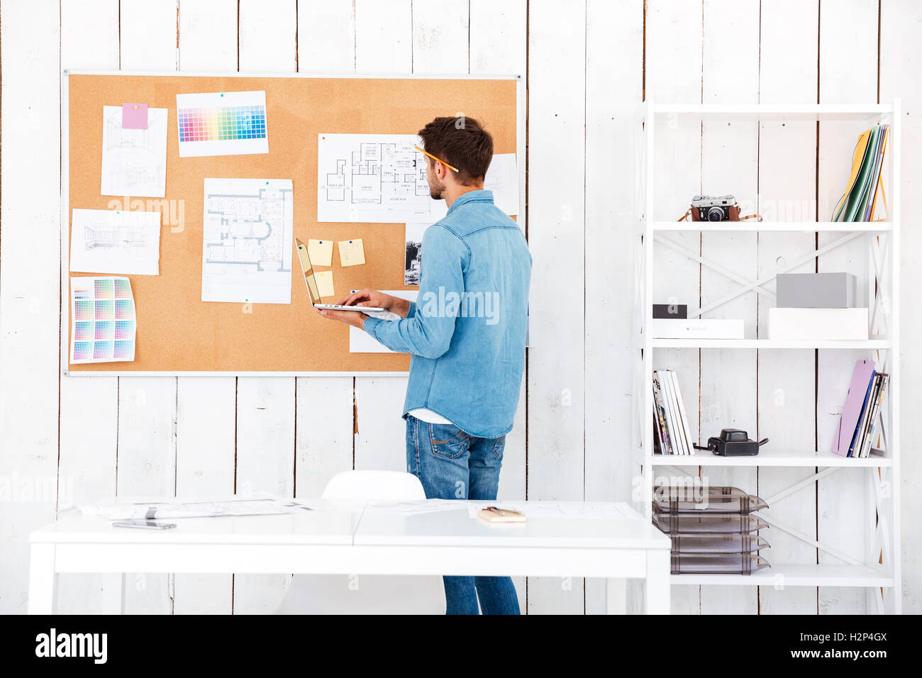 Back view of a concentrated young man looking at the task board and using laptop while standing in office Stock Photo