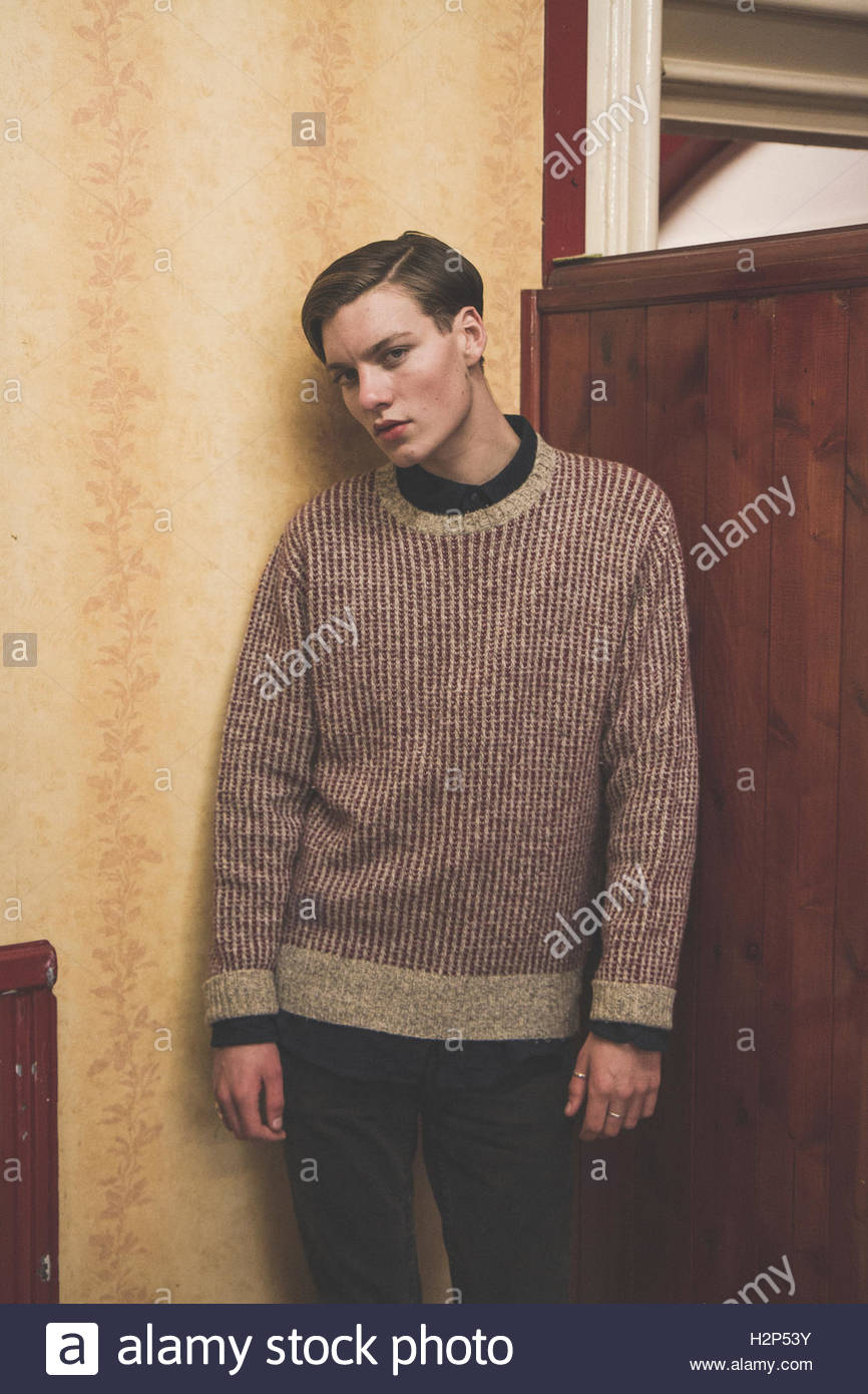 young guy hanging out in a social club wearing a knitted jumper, black jeans and doc martens, Stock Photo