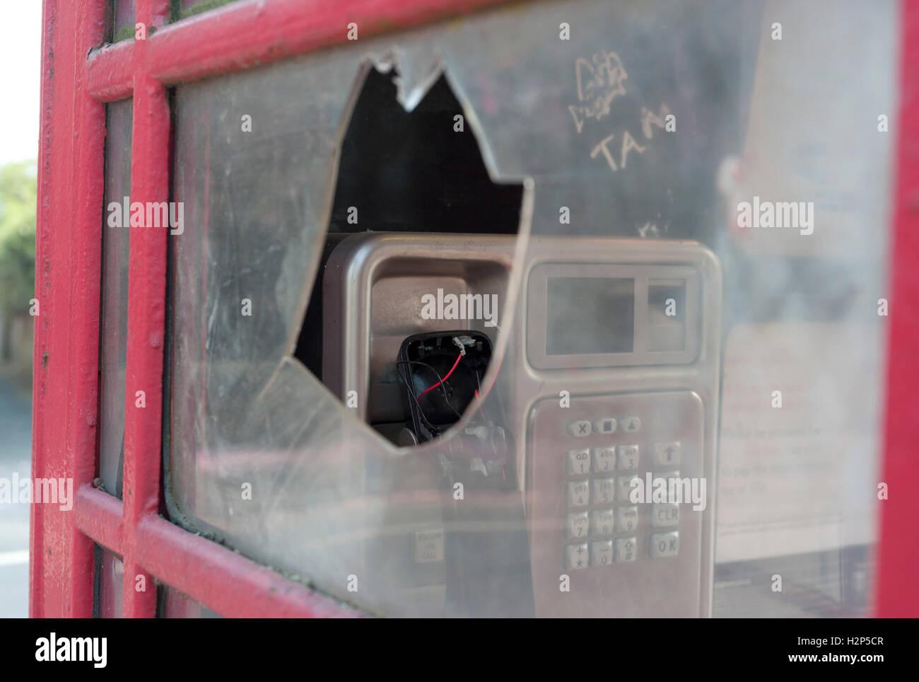 Vandalized telephone box. - Stock Image