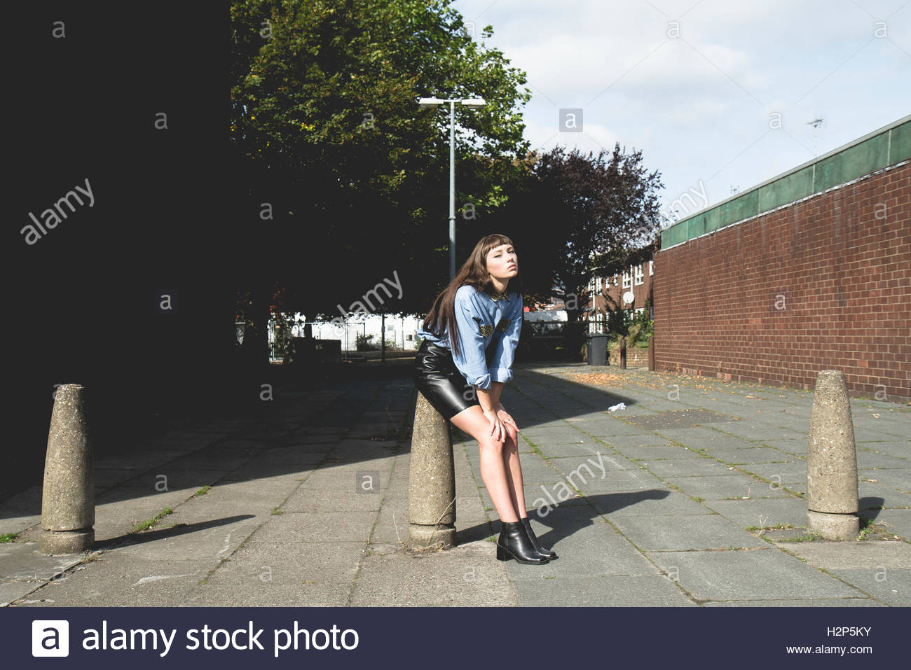 Brunette model with a fringe wears a light blue denim shirt and a black leather skirt in front of a brick wall and - Stock Image