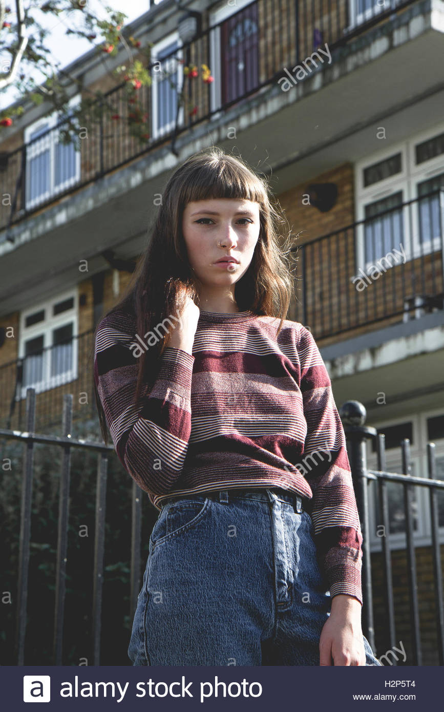 brunette Model with fringe in front of flats wearing a striped long sleeved t shirt and blue denim jeans and black - Stock Image