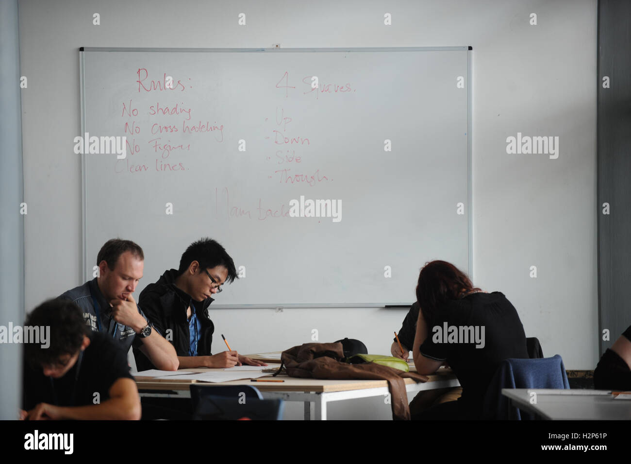 College students get their heads down and work hard on their education in a college classroom with whiteboard behind. - Stock Image
