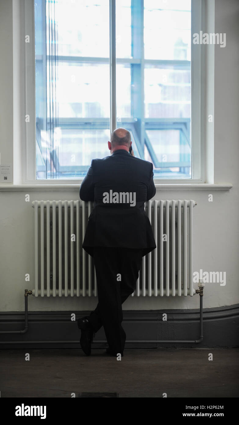A man in a suit make a phonecall in a corroder whilst waiting outside a room. - Stock Image