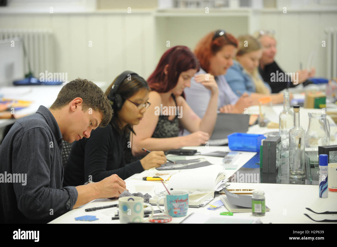 College students get their heads down and work hard on their education in a college classroom. - Stock Image