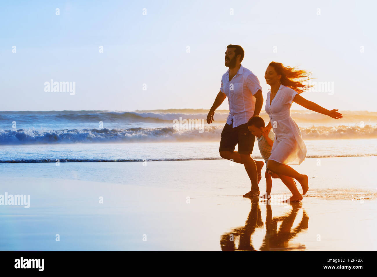 Happy family - father, mother, baby son hold hands and run together with fun along sunset sea surf on black sand - Stock Image