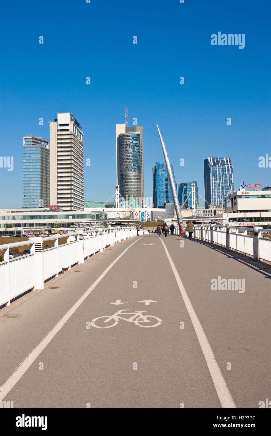Vilnius, Lithuania - March 16, 2015: White bridge - pedestrian and bicycle bridge across Neris river, modern buildings. Stock Photo