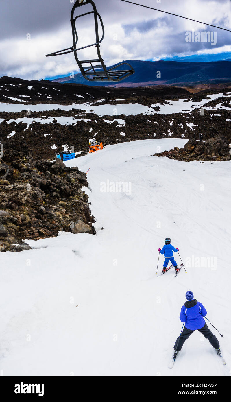 Father and son ski downhill from to top of mount Ruapehu - Stock Image