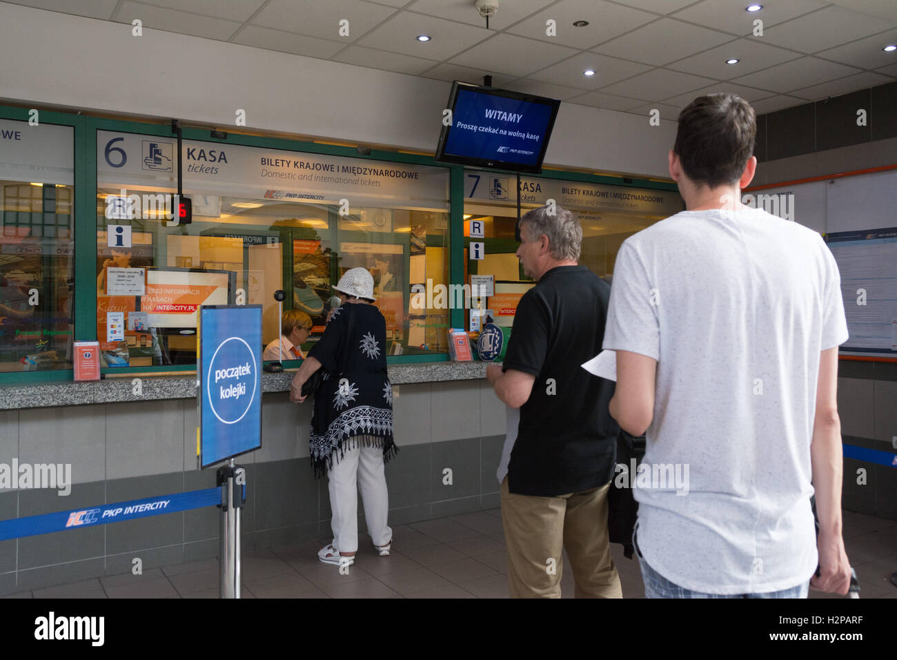woman buying tickets from the ticket desk at Glowny station, Gdansk, Poland - Stock Image