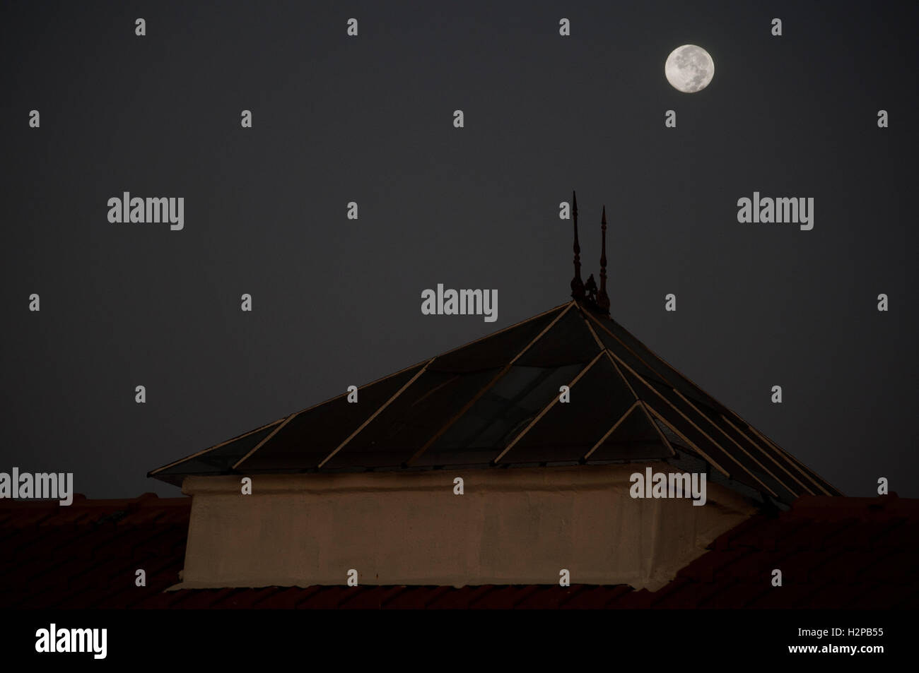 Full moon over the roof - Stock Image