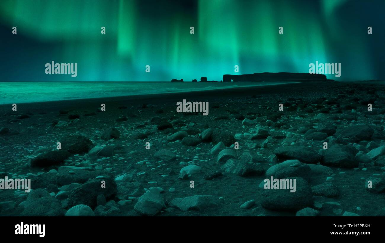 Composite photo showing the Northern Lights (Aurora Borealis) seen from Vik beach in Iceland. Vik beach, known locally - Stock Image