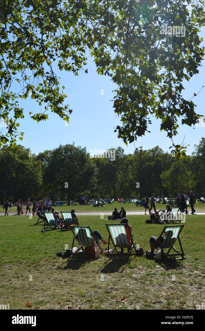 Crowds enjoying a sunny day in Green Park, London, England. - Stock Image