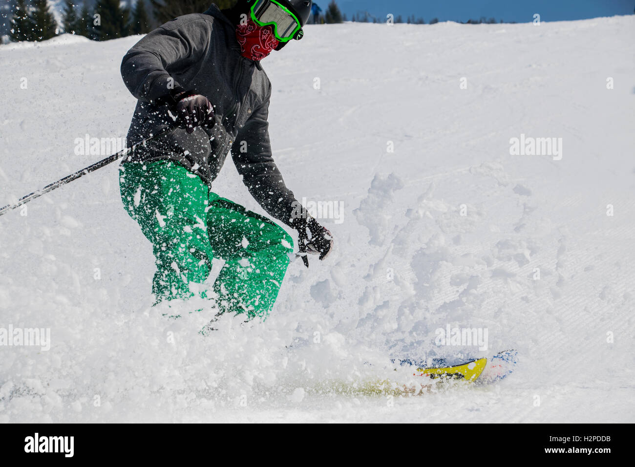 skier produces a snow cloud when stopping downhill trip - Stock Image