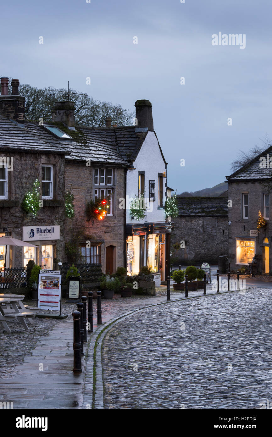 Colourful Christmas lights brighten up a dark winter's evening - Grassington Village, Yorkshire Dales National Park, England. Stock Photo