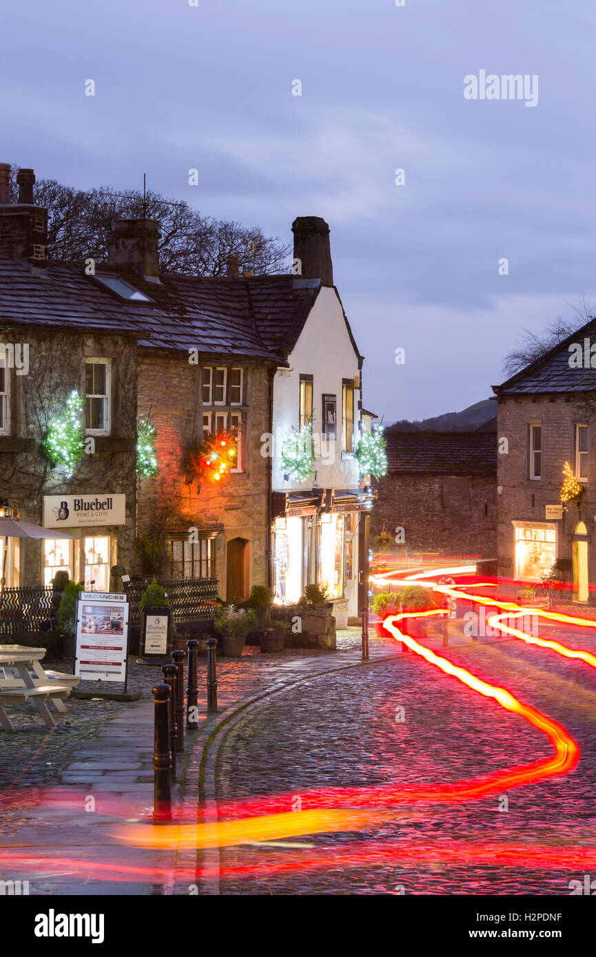 Both Christmas and trail lights add colour on a dark winter night - Grassington Village, Yorkshire Dales National Park, England. Stock Photo