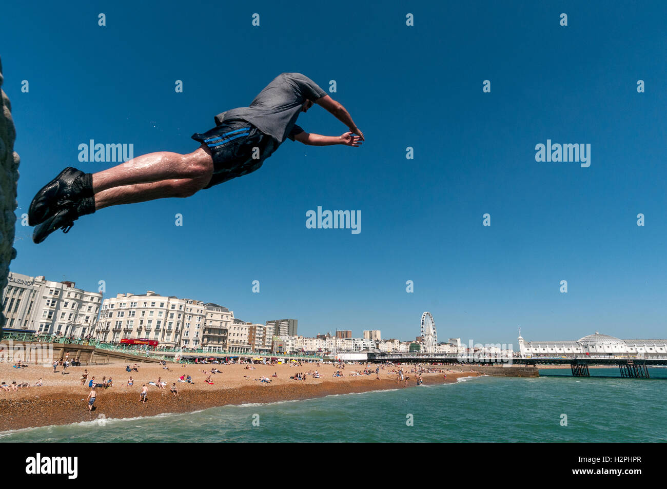 Teenagers jumping from groynes on Brighton beach into the sea on a hot afternoon. - Stock Image