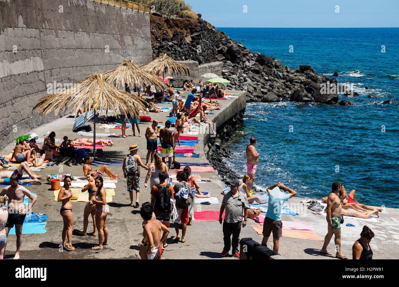 People enjoy the summer weather going swimming in the atlantic ocean at the rocky beach of Jardim do Mar - Stock Image