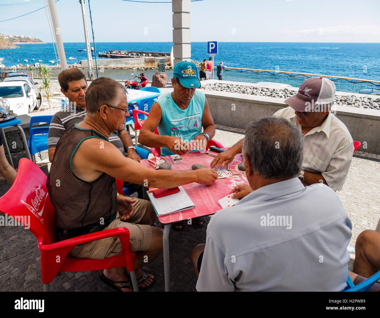 Five men enjoy a game of cards by the sea at the village of Paul do Mar - Stock Image