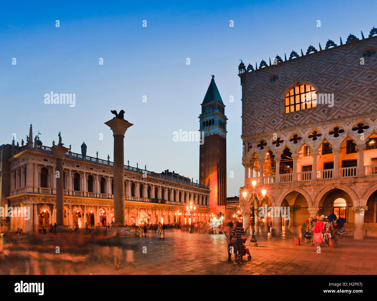 Doges palace, Campanile bell tower and Venice republic coat of arms lion on tall column at San Marco square at sunset - Stock Image