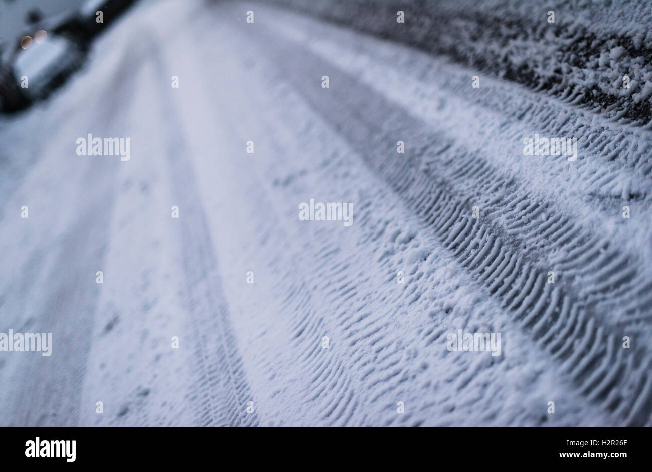 Tracks of car tires on a snow covered, glazed, icy street during a cold winter night Stock Photo