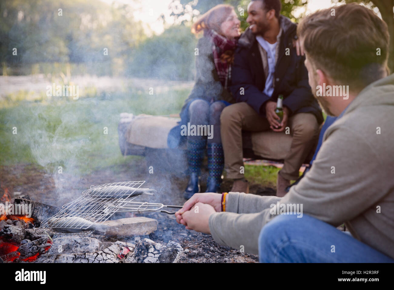 Friends Cooking Fish In Grill Basket Over Campfire