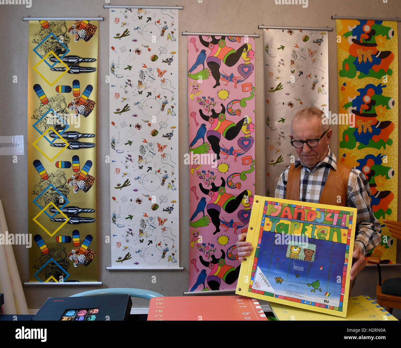 Celle, Germany. 16th Sep, 2016. Hans-Heinrich Stumpf presents a wallpaper catalogue by illustrator Janosch at the Stock Photo
