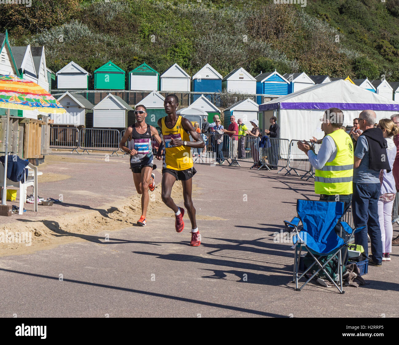 Runners and spectators at the annual Bournemouth marathon on the promenade, West Beach in fine weather, Dorset, - Stock Image