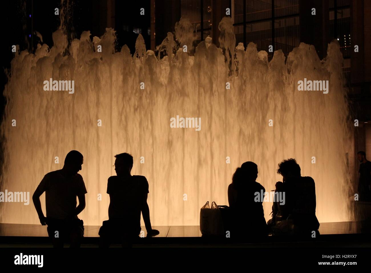 Four human silhouettes seen against illuminated Revson Fountain at Lincoln Center Plaza, New York. - Stock Image