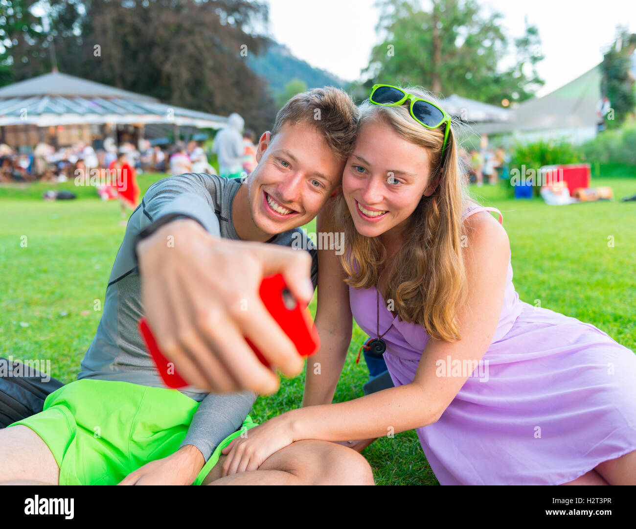 Young man and young woman smiling, taking photo with mobile phone, selfie, Bavaria, Germany - Stock Image