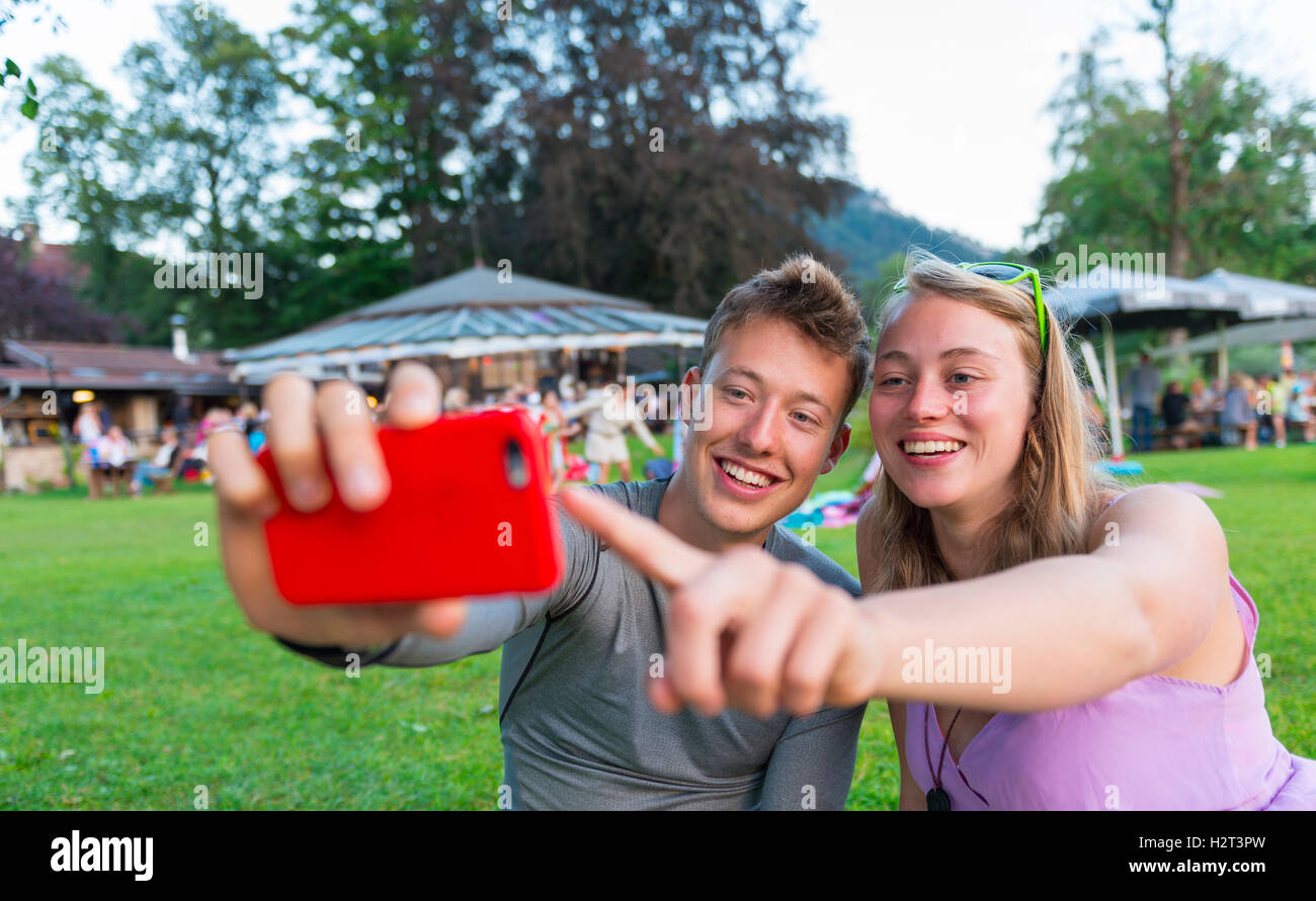 Young man and young woman smiling, looking at mobile phone, Bavaria, Germany - Stock Image