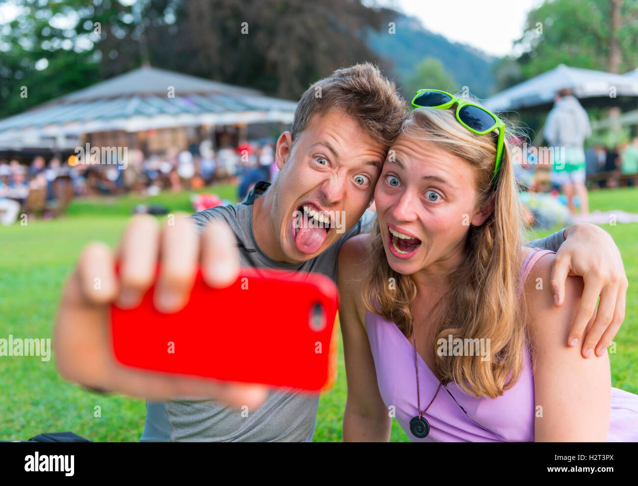 Young man and young woman making faces, taking photo with mobile phone, selfie, Bavaria, Germany - Stock Image