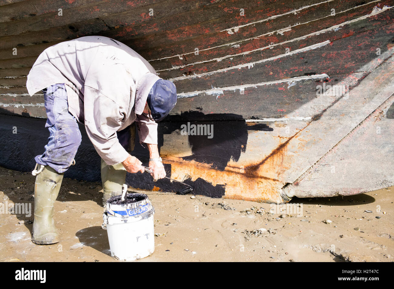 An 'old-salt' applying anti-fouling paint to the keel of his yacht, Conwy beach, Wales, UK - Stock Image
