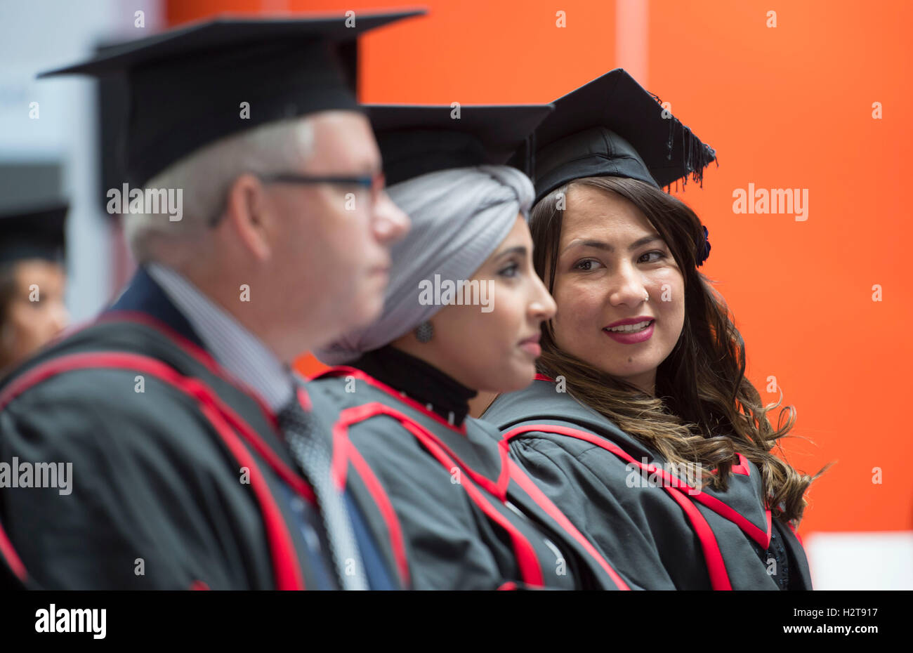 University degree students wearing mortarboards and gowns during a graduation ceremony. - Stock Image
