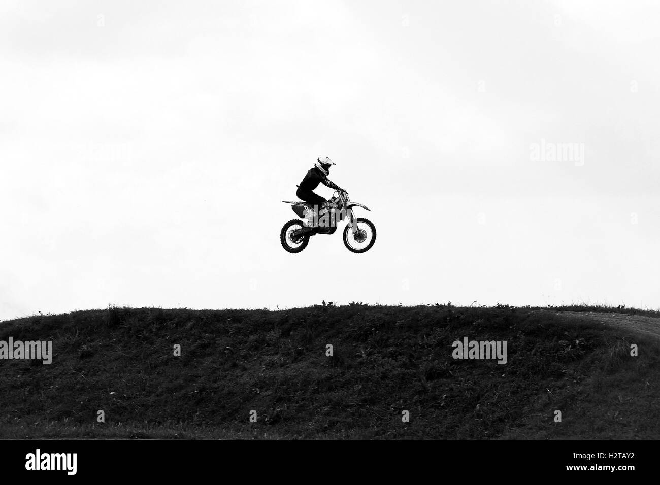 Motorbike jumping in the sky on hide speed black and white photo - Stock Image