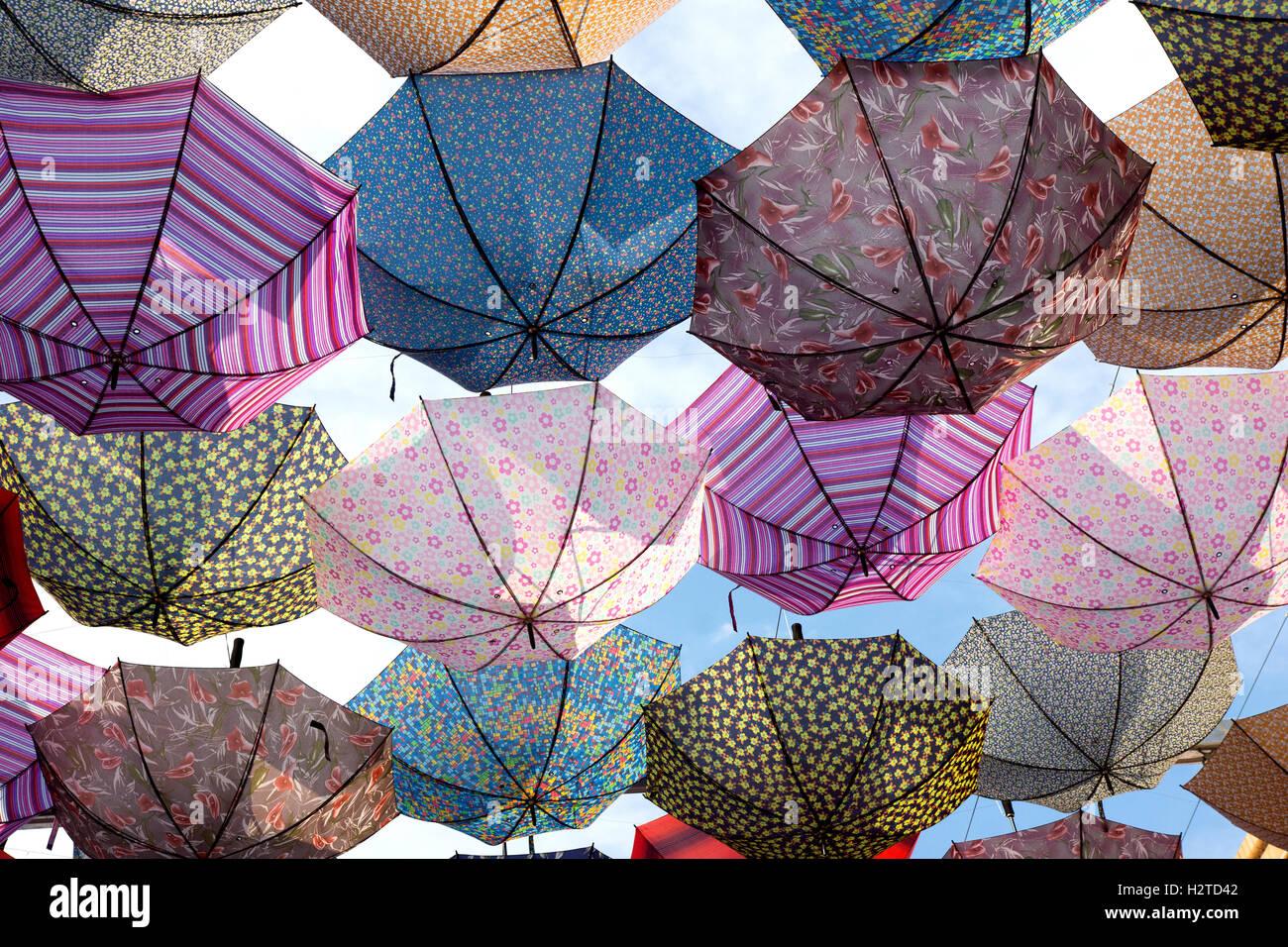 Colorful umbrellas flying in the sky - Stock Image