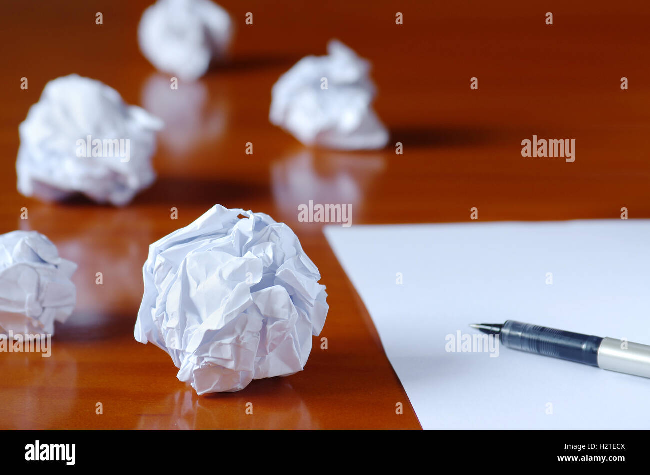 Paper balls and pen over blank white sheet - Creativity crisis concept - Stock Image